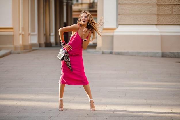 Alta altura cheia de estatura elegante sorridente feliz mulher atraente com vestido rosa sexy de verão cabelo comprido andando na rua segurando bolsa