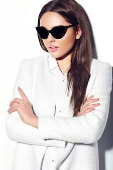 Alta moda look.glamor closeup retrato do modelo de negócios morena sexy elegante jovem mulher bonita no pano de hipster jaqueta casaco branco em óculos de sol