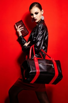 Alta moda look.glamor closeup retrato do modelo sexy caucasiano elegante morena jovem bonita jaqueta preta com maquiagem brilhante de saco, com lábios vermelhos, com perfeita pele limpa em estúdio