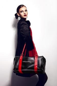 Alta moda look.glamor closeup retrato do modelo sexy caucasiano elegante morena jovem bonita vestido vermelho com maquiagem brilhante bolsa preta, com lábios vermelhos, com pele limpa perfeita em estúdio