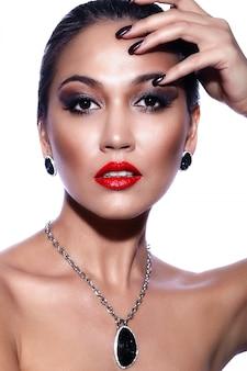 Alta moda look.glamor closeup retrato do modelo sexy caucasiano morena jovem bonita com maquiagem brilhante, com lábios vermelhos, com pele limpa perfeita com joias isolada no branco