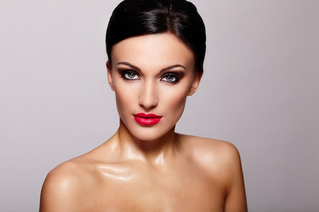 Alta moda look.glamor closeup retrato do modelo sexy caucasiano mulher jovem e bonita com lábios vermelhos, maquiagem brilhante, com perfeita pele limpa isolada em cinza