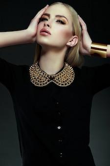 Alta moda look.glamor closeup retrato do modelo sexy elegante loira jovem bonita com maquiagem amarela brilhante com pele limpa perfeita com jóias de ouro em pano preto