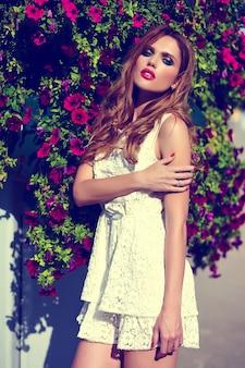 Alta moda look.glamor closeup retrato do modelo sexy elegante loira jovem bonita com maquiagem brilhante e lábios cor de rosa com perfeita pele limpa no chapéu perto de flores do verão