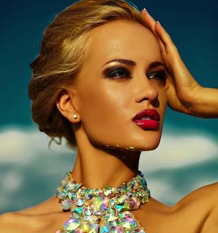 Alta moda look.glamor closeup retrato do modelo sexy elegante loira jovem bonita com maquiagem brilhante e lábios vermelhos com pele limpa banhos de sol perfeita com jóias ao ar livre no estilo da moda
