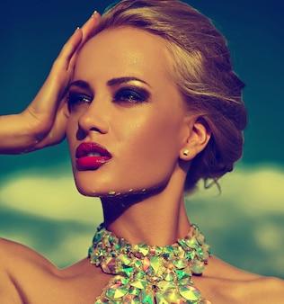 Alta moda look.glamor closeup retrato do modelo sexy elegante loira jovem bonita com maquiagem brilhante e lábios vermelhos com pele limpa banhos de sol perfeita com jóias ao ar livre no estilo de moda em e