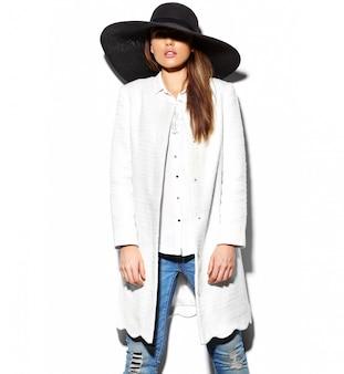 Alta moda look.glamor closeup retrato do modelo sexy elegante morena sexy jovem mulher de casaco branco jaqueta e grande chapéu preto