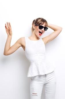 Alta moda look.glamor elegante bela jovem modelo feminino com lábios vermelhos em tecido colorido brilhante de verão branco e óculos de sol hipster. o largo sorriso branco