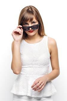Alta moda look.glamor elegante bela jovem modelo feminino com lábios vermelhos em tecido colorido brilhante de verão branco e óculos de sol hipster.