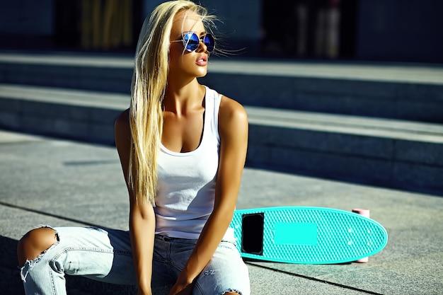 Alta moda look.glamor elegante sexy modelo loiro jovem garota com roupas de hipster casual brilhante de verão com skate sentado na rua
