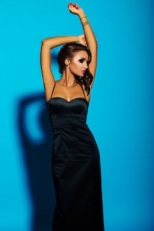 Alta moda look.glamor retrato do modelo sexy caucasiano mulher jovem e bonita elegante vestido preto com lábios rosa, maquiagem brilhante, com pele limpa banhos de sol perfeita, isolada no azul