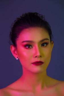 Alta moda modelo mulher em luzes brilhantes coloridas posando