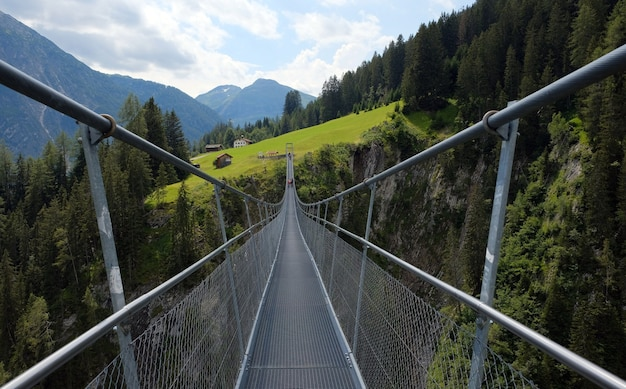 Alta ponte suspensa entre montanhas, árvores e rochas em lechtal, lech, áustria