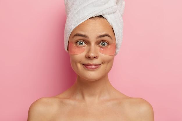 Alta resolução. foto na cabeça de uma linda jovem surpresa com pele saudável e fresca, usa adesivos anti-rugas embaixo dos olhos, fica de pé com os ombros nus, olha com firmeza, visita o centro de spa