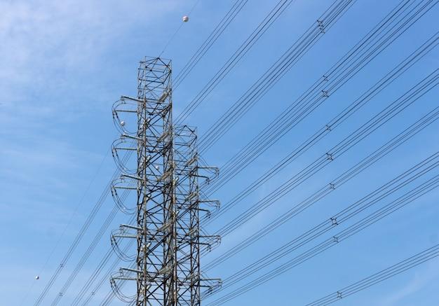 Alta tensão de torres de transmissão de energia no fundo do céu azul
