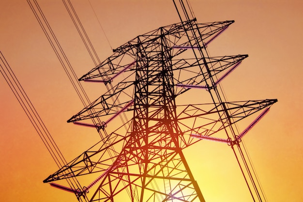 Alta tensão do polo da eletricidade com cabo no céu e na luz solar amarelos conceito da tecnologia.
