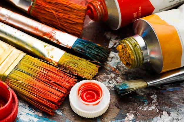 Alta vista de tintas e pincéis coloridos
