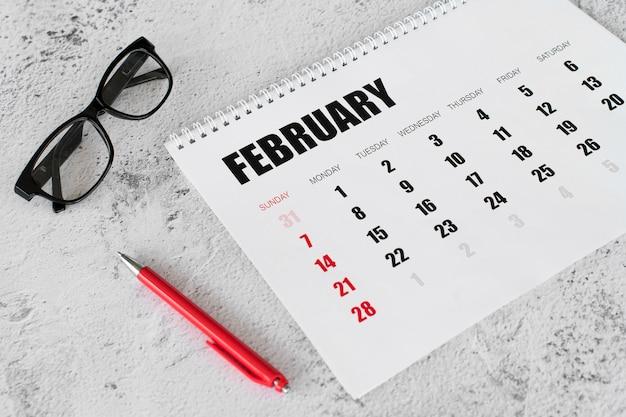 Alta visualização do calendário do mês de fevereiro e óculos de leitura
