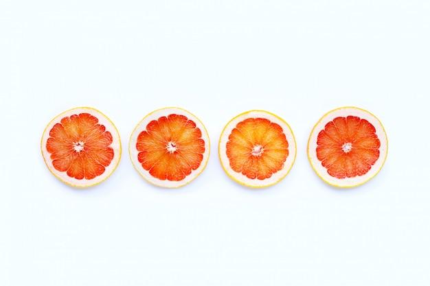 Alta vitamina c. fatias de toranja suculentas em fundo branco.