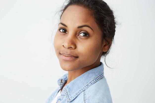 Altamente detalhado close-up retrato de linda mulher afro-americana com perfeita pele limpa e olhos roxos, com expressão de rosto calmo na parede branca.