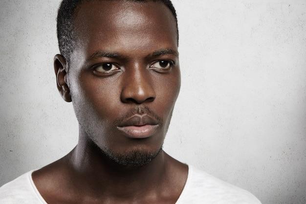 Altamente detalhado close-up tiro de homem africano olhando sério e confiante, isolado contra uma parede branca de pé.