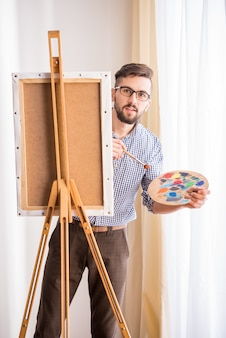 Altamente talentoso pintor está segurando pincel e paleta.
