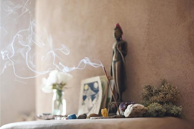 Altar com pedras e incenso no interior da casa de adobe