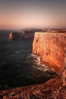 Altas falésias vermelhas ao redor do cabo de são vicente, no canto sudoeste de portugal, na região do algarve