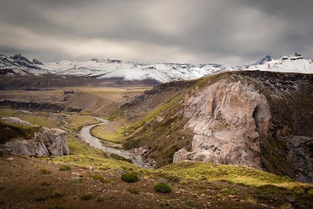 Altas montanhas cobertas de neve sob o céu nublado