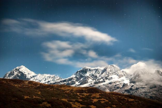 Altas montanhas sob o céu azul escuro com estrelas. kangchenjunga, índia.