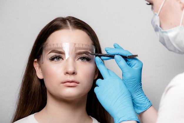 Alterando a forma das sobrancelhas. estilista medindo as sobrancelhas com a régua.