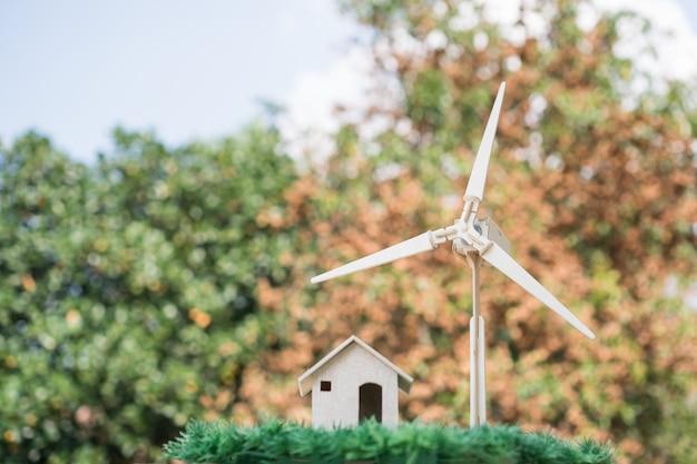 Alternativa de energia futura, conceito de energia elétrica limpa / renovável. casa / turbina eólica que mostra o uso de energias verdes no fundo de orage. alternativa de preservação da natureza ou meio ambiente