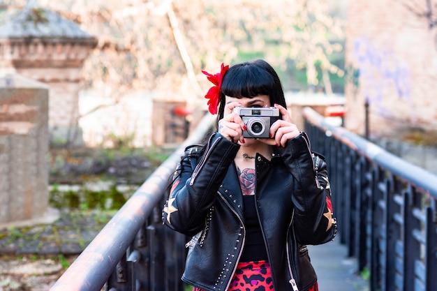Alternativa mulher tatuada com jaqueta de couro e uma flor no cabelo, tirando uma foto em uma ponte com uma câmera vintage.