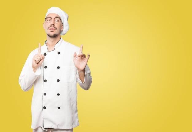 Altivo jovem chef fazendo um gesto desdenhoso