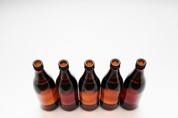 Alto ângulo alinhado garrafas de cerveja no fundo branco, com espaço de cópia