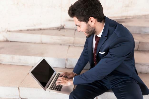 Alto ângulo, assento homem, ligado, escadas, com, laptop