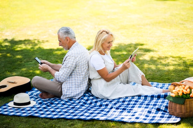 Alto ângulo casal verificando seus dispositivos