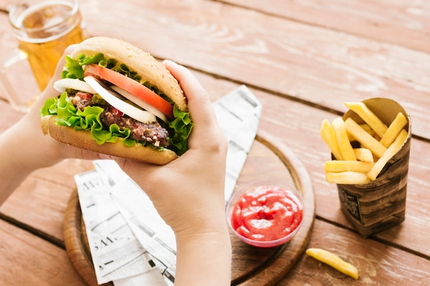 Alto ângulo, close-up, mãos, segurando, hambúrguer, com, hambúrguer, com, frita