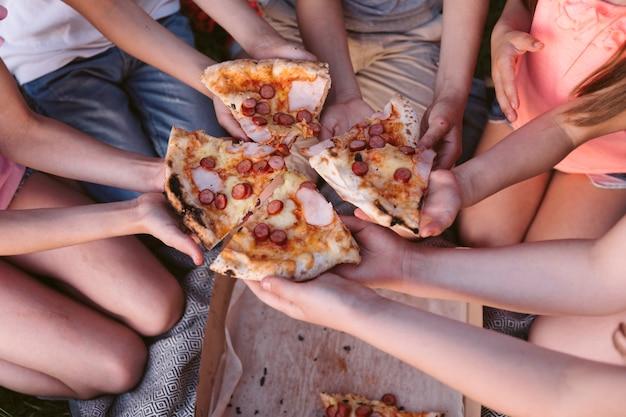 Alto ângulo, crianças, levando, um, fatia pizza