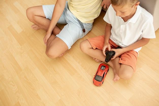 Alto ângulo, crianças, tocando, com, um, carro elétrico