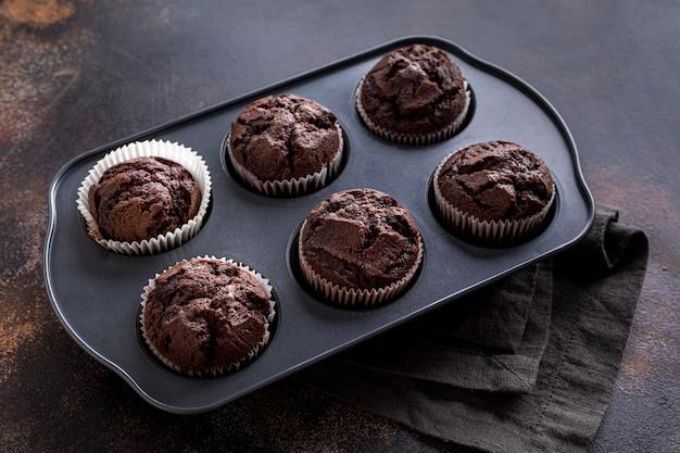 Alto ângulo da bandeja com bolos e pano de chocolate