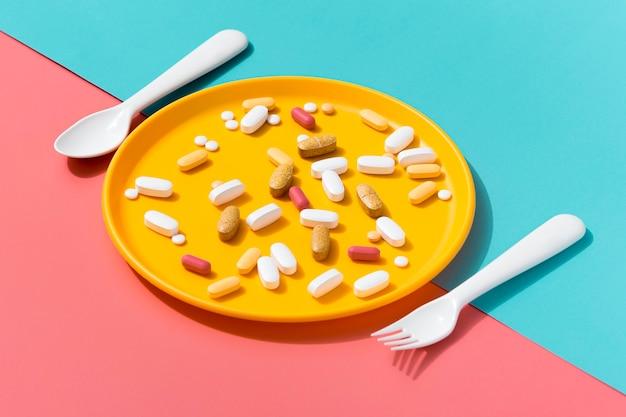 Alto ângulo da bandeja com pílulas e talheres