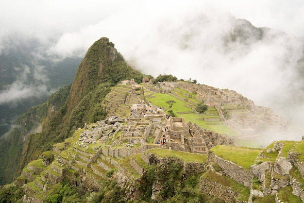 Alto ângulo da bela cidadela de machu picchu, rodeado por montanhas nubladas em urubamba, peru