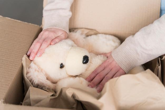 Alto ângulo da caixa com o ursinho de pelúcia sendo preparado para ser enviado
