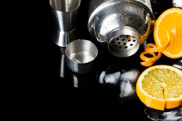 Alto ângulo da coqueteleira com cubos de laranja e gelo