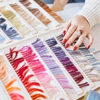 Alto ângulo da estilista feminina trabalhando no ateliê com paleta de cores