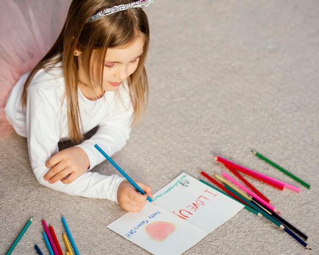 Alto ângulo da garota segurando o cartão de desenho para o dia dos pais