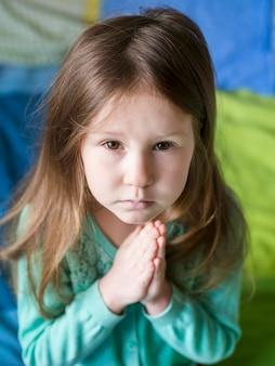 Alto ângulo da linda garotinha rezando