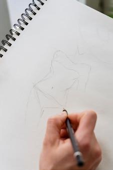 Alto ângulo da mão feminina desenhando no caderno