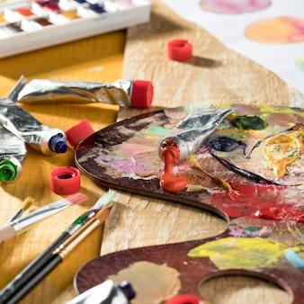 Alto ângulo da paleta de pintura com tintas e pincéis coloridos